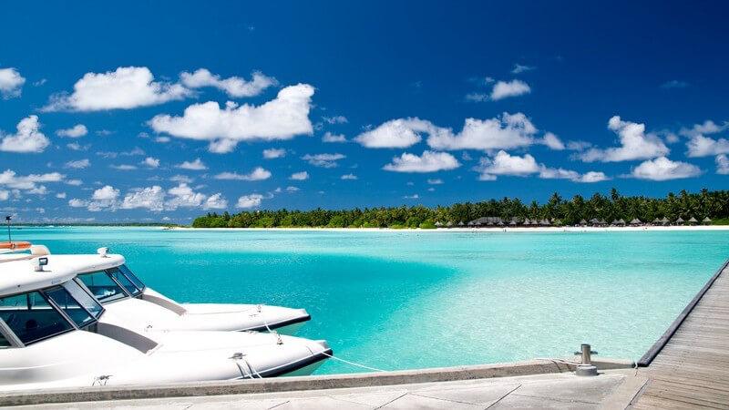 Zwei weiße Luxusyachten haben an Inselhafen angelegt, türkises Wasser, Strand und Palmen im Hintergrund, blauer Himmel