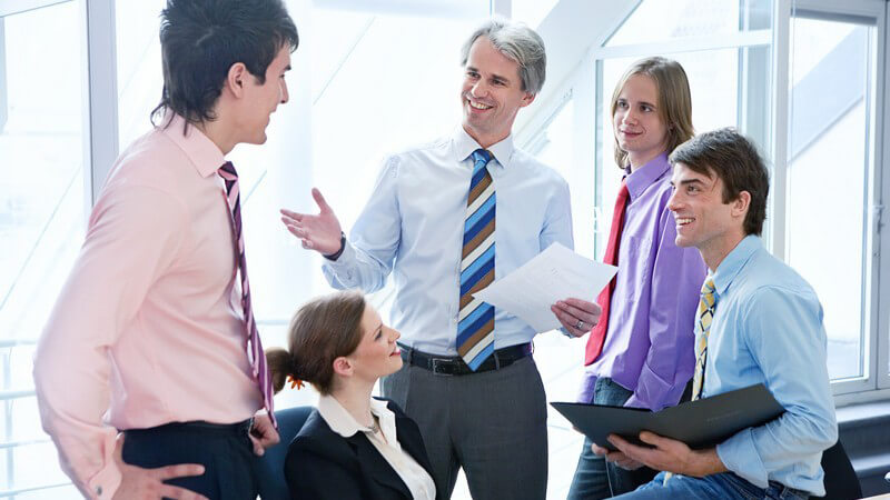 Kleine Gruppe im Businesslook bei lockerem Meeting im Büro