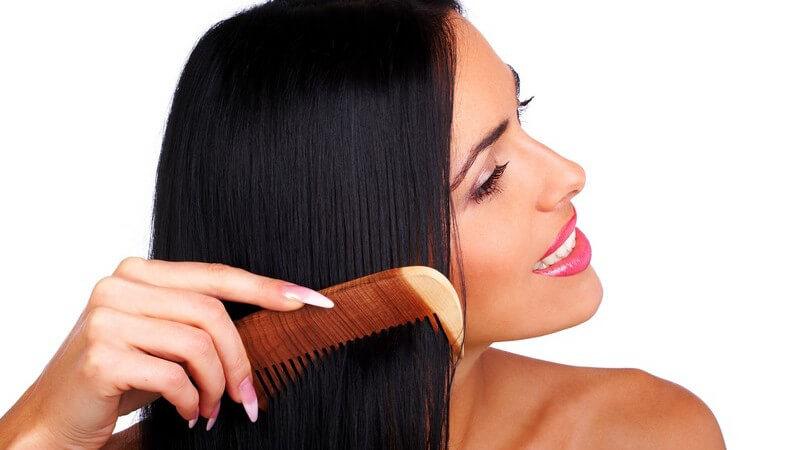 Frau mit langen schwarzen Haaren und rosa Lippenstift kämmt ihre Haare mit braunem Kamm