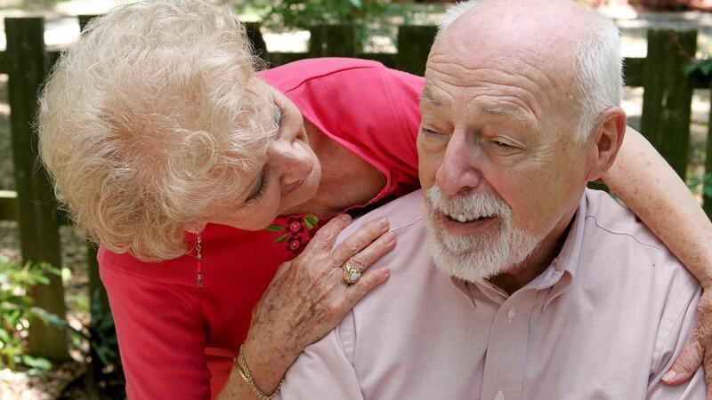 Blonde, alte Frau steht fürsorglich hinter ihrem Partner und umarmt ihn