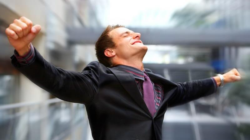 Mann im Anzug streckt Arme aus und schaut glücklich nach oben, Hintergrund verschwommen