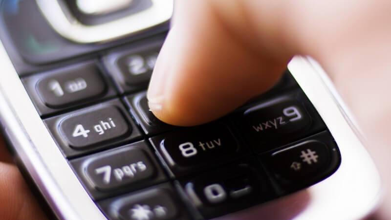 Nahaufnahme von Testatur eines Handys mit Daumen einer Männerhand, silbernes Mobiltelefon mit schwarzen Tasten