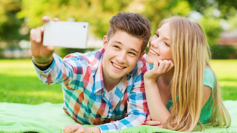 Selfie: junges Paar liegt im Park auf einer Wiese und macht ein Foto mit dem Handy