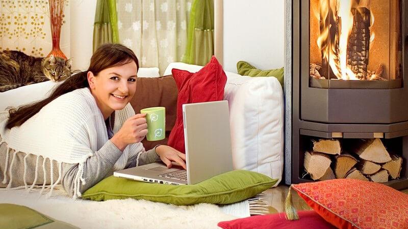Frau liegt mit Notebook und Tasse Kaffe vor Kaminfeuer im Wohnzimmer