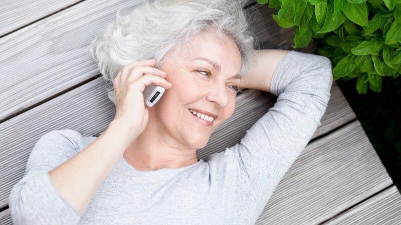 Ältere Frau beim Telefonieren, sie lächelt und sieht glücklich aus