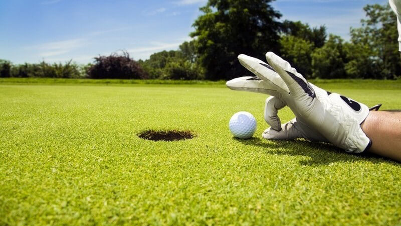 Golfloch, Golfball und Hand mit Golfhandschuhen, Zeigefinger und Daumen zum Kreis geformt
