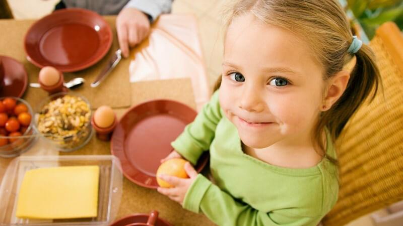 Ansicht von oben: kleines Mädchen mit Familie am Tisch beim Frühstück