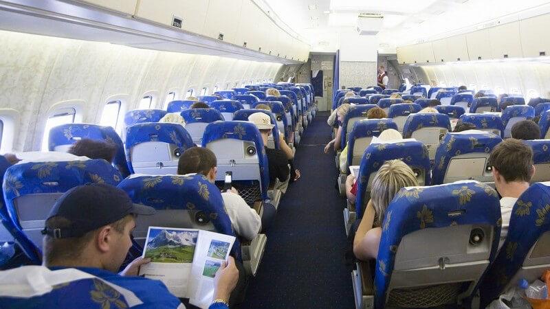 Rückansicht Gang im Innenraum eines Flugzeuges, mehrere Menschen in Sitzreihen