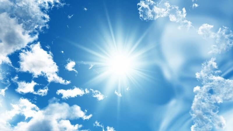 Blauer Himmel mit Wolken und strahlend heller Sonne