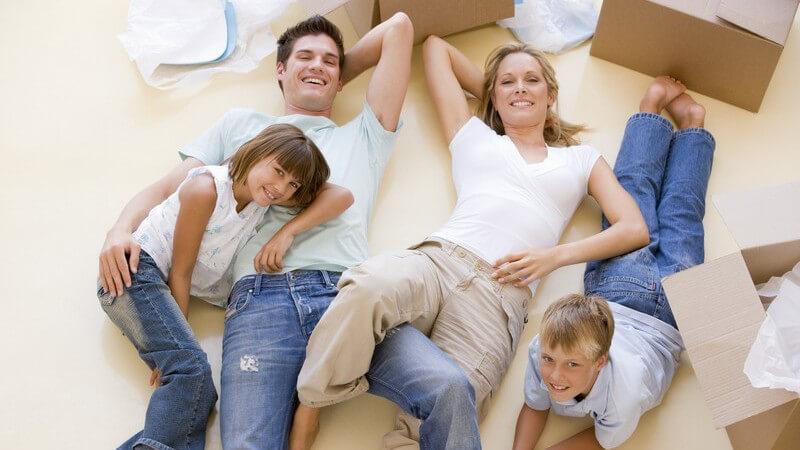 Junge lächelnde Familie liegt im neuen Zuhause zwischen Umzugskartons auf dem Boden