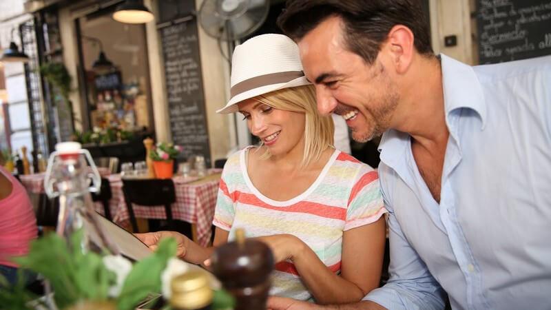 Paar im Sommerurlaub sitzt im Restaurant und schaut Speisekarte durch