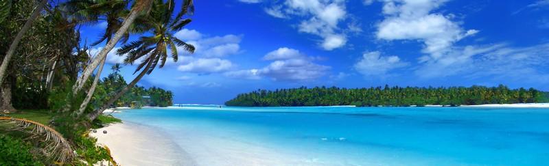 Panorama von Lagune mit Palmen im linken Vordergrund, weißem Strand und azurblauem Meer
