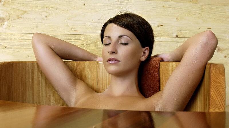 Junge, dunkelhaarige Frau entspannt in Holzbadewanne, die Arme hiter Kopf über Wannenrand