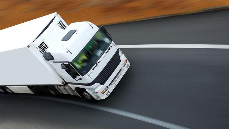 Weißer Lastwagen von vorne oben fährt auf Straße