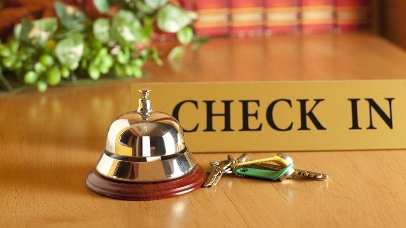 """Hotelempfang, Rezeption mit Zimmerschlüssel, """"Check in""""-Schild und Klingel"""