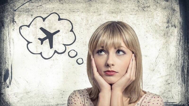 Flugangst: Junge Frau hält sich Hände ans Gesicht, schaut besorgt, Gedankenblase mit Flugzeug darin