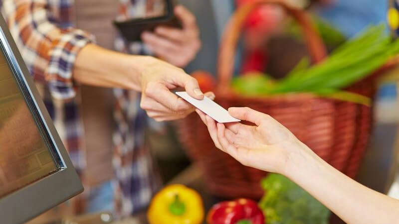 Bezahlen an der Supermarkt-Kasse: Frau reicht Kassiererin eine Kundenkarte oder eine Geldkarte