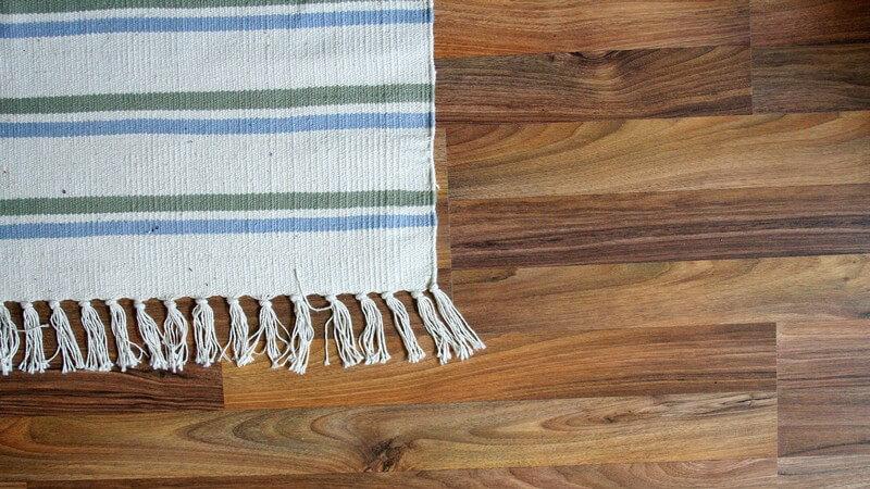 Ausschnitt weißer Teppich mit grünen und blauen Streifen auf dunklem Holzboden