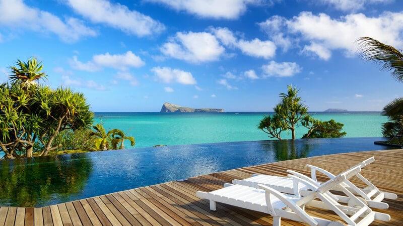 Mauritius: Blick von Holzterasse mit Liegestühlen und Infinity-Pool auf das türkise Meer, Sommerurlaub