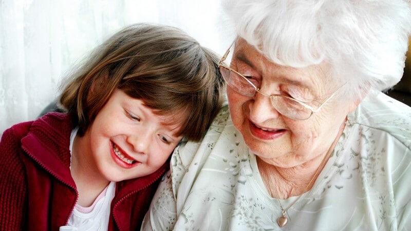 Großmutter mit Brille, links junge Enkelin in rotem Pullover