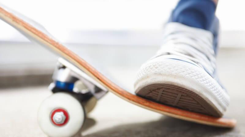Weißer Turnschuh drückt Ende eines Skateboards nach unten