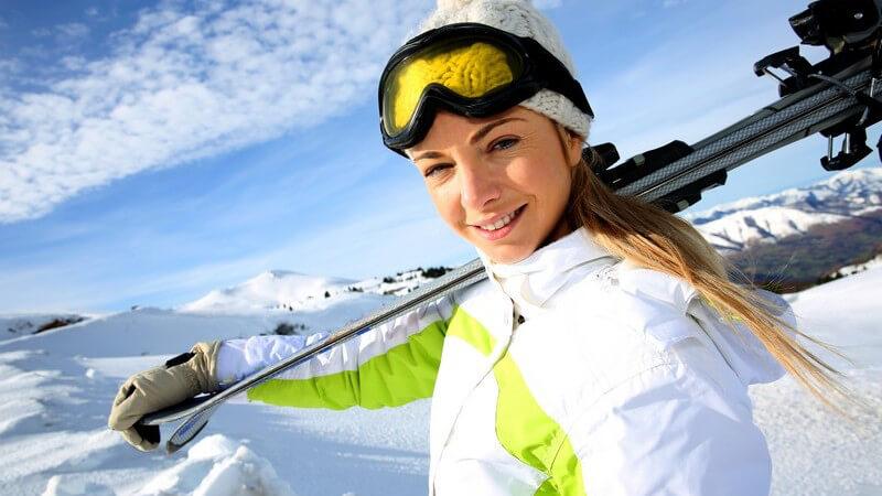 Frau mit Skiern über der Schulter, im Hintergrund Skipiste, Skigebiet