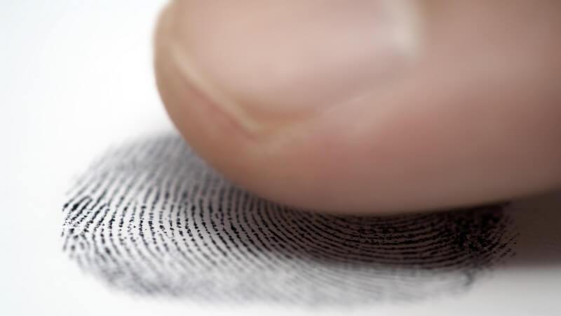 Finger hinterlässt schwarzen Fingerabdruck auf weißem Untergrund