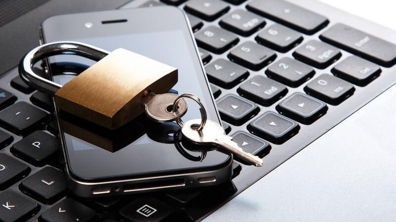 Vorhängeschloss mit Schlüssel liegt auf schwarzem Smartphone und Tastatur