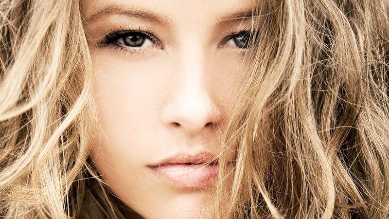 Gesichtsportrait junge schöne Frau mit langen gelockten blonden Haaren