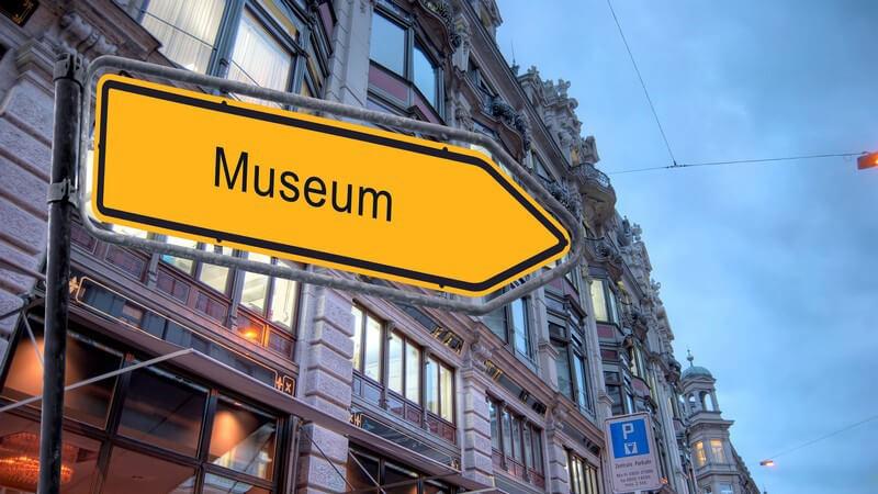 """Gelbes Wegweiserschild mit der Aufschrift """"Museum"""" in Innenstadt"""