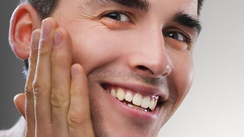 Junger Mann trägt lächelnd After shave auf