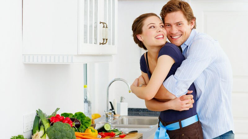 Junges Liebespaar in Küche, Umarmung, auf der Arbeitsfläche viel Gemüse, weiße Oberschränke, helle Küche, Spüle