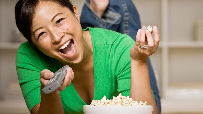 Junge, lachende Frau liegt mit Schüssel Popcorn auf dem Bauch und schaut Fern