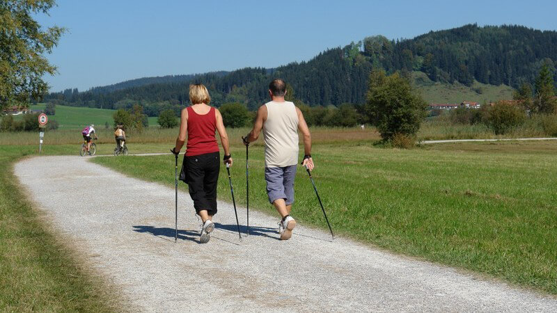 Rückansicht Paar beim Nordic Walking auf Feldweg