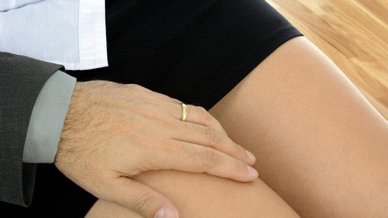 Geschäftsmann grabscht einer Geschäftsfrau in schwarzem Rock an den Oberschenkel