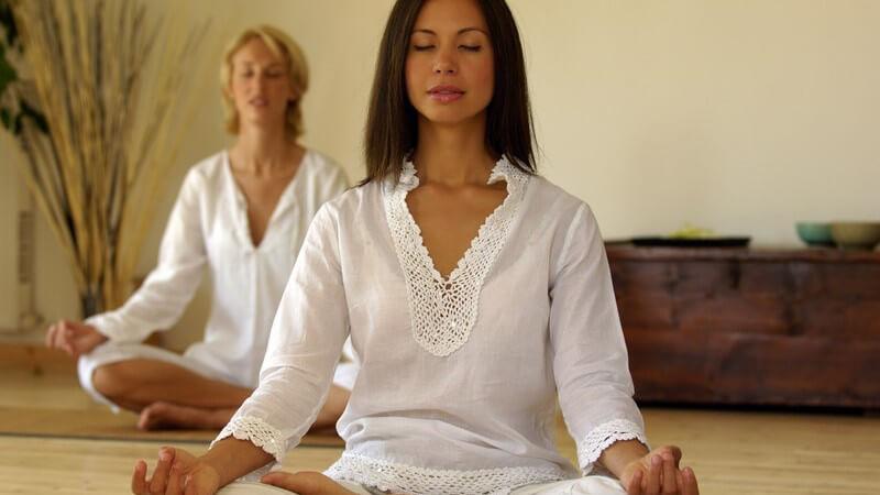 Zwei Frauen sitzen im Schneidersitz auf dem Boden und meditieren