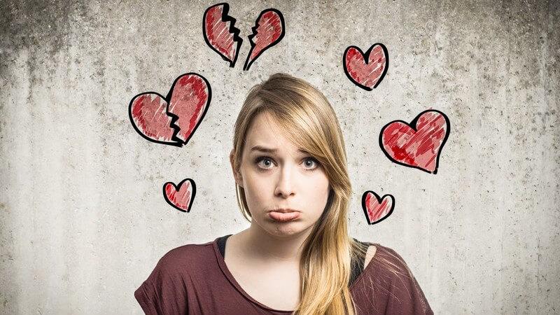 Mädchen guckt betrübt und verwirrt, um sie herum teils gebrochene rote Herzen, Liebeschaos