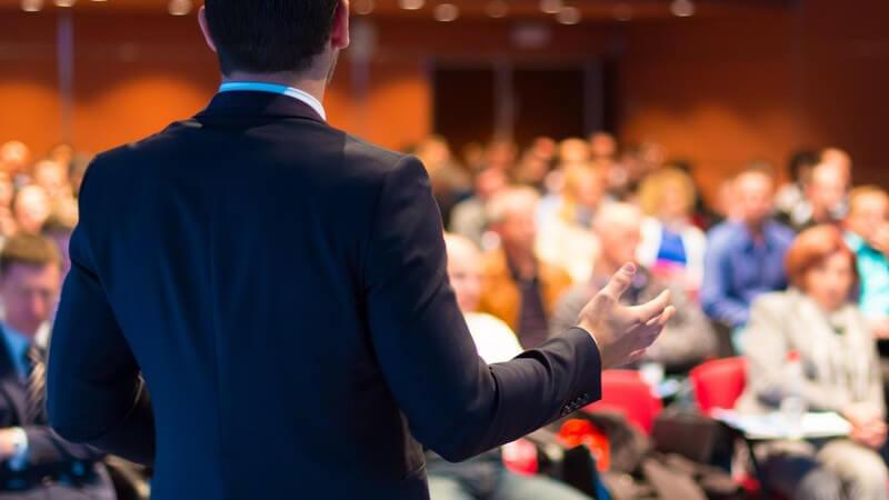Rückansicht eines Sprechers in einem Hörsaal, im Hintergrund das Publikum