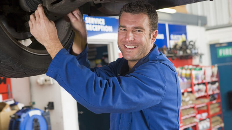 Automechaniker im Blaumann an Hebebühne unter Auto, lächelnd
