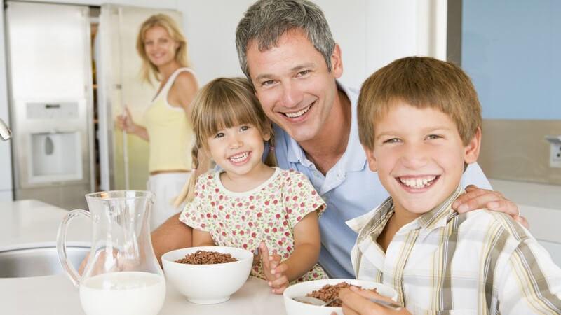Vater mit zwei kleinen Kindern beim Frühstückstisch, im Hintergrund Mutter an Kühlschranktür