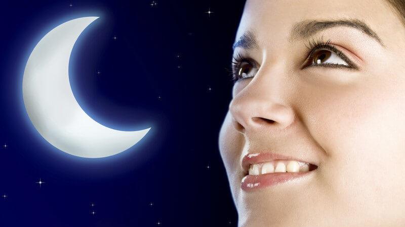 Junge Frau schaut lächelnd in den Himmel, im Hintergrund Grafik Halbmond und Sterne