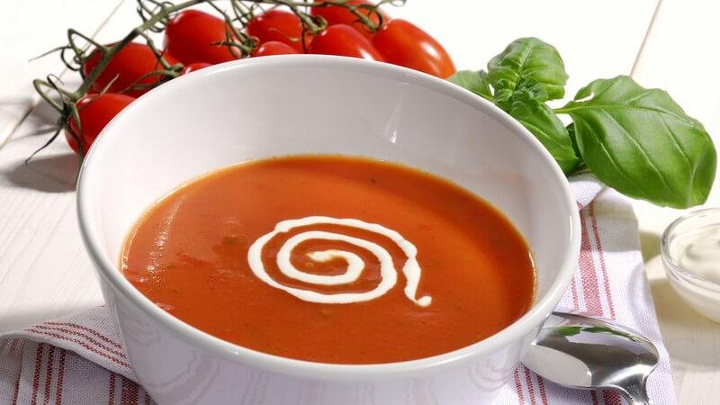 Teller mit Tomatensuppe auf Tisch, daneben frische Tomaten mit Basilikum
