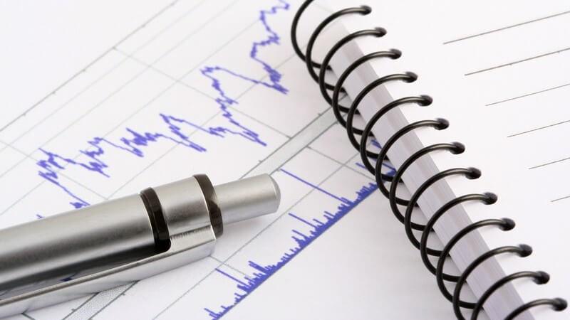 Silberner Kugelschreiber auf Aktiendiagramm mit weißem Ringblock