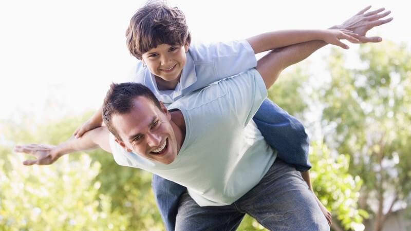 Junger Vater trägt seinen Sohn auf dem Rücken und spielt mit ihm Flieger