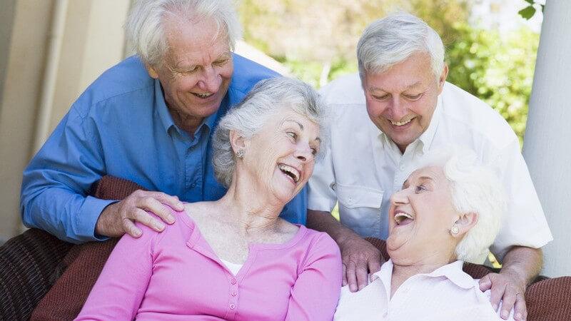 Zwei befreundete alte Paare lachen gemeinsam