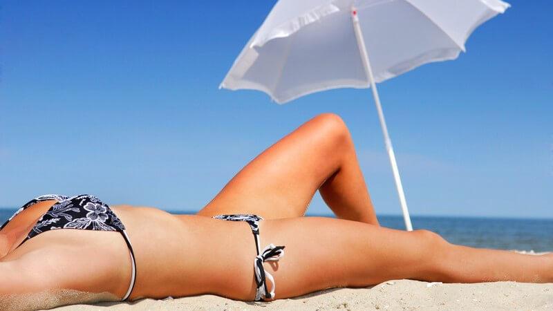 Frauenkörper im Bikini vor weißem Sonnenschirm am Strand