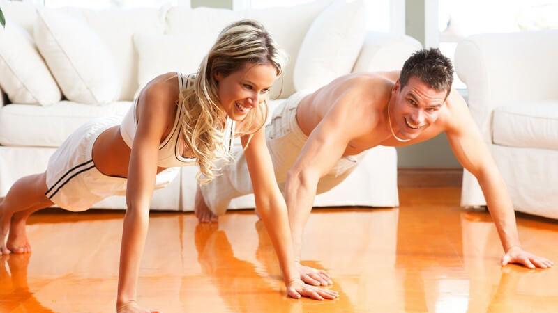 Junges, lächelndes Paar im Sportoutfit macht Liegestütze