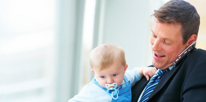 Geschäftsmann hält ein Baby auf dem Arm und telefoniert mit seinem Handy