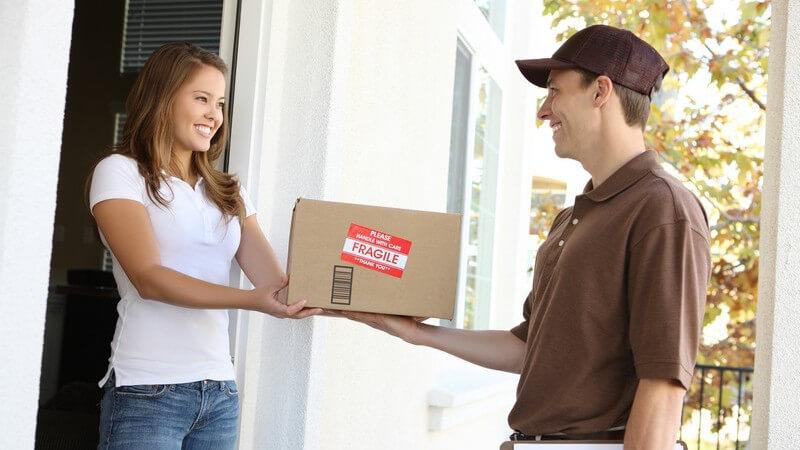 Lieferant bringt junger Frau ein Päckchen