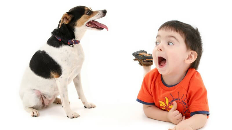 Kleiner Junge mit aufgerissenem Mund liegt auf dem Bauch neben einem Hund